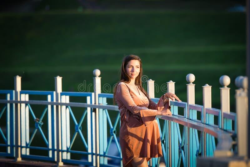 Girl posing on the promenade. A girl walks along the promenade. A young girl walks past the fence stock photography