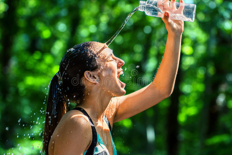 Girl pouring water on face after workout. royalty free stock photo