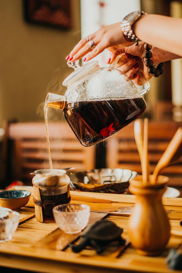 Girl pours fresh green tea in coffee. Girl pours freshly brewed tea in coffee stock photos