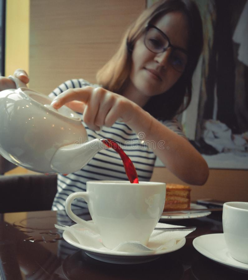 The girl pours tea into a cup from white kettle stock photography