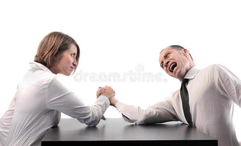 Girl power. Businesswoman winning at arm wrestling against a businessman royalty free stock photo