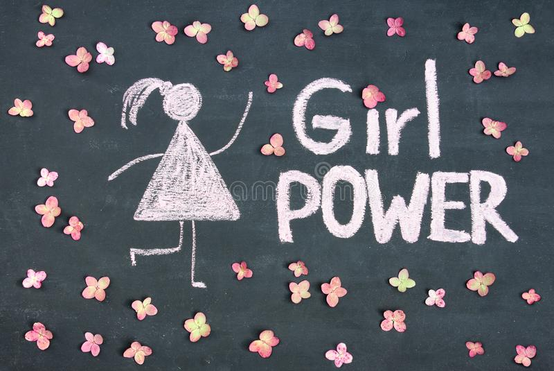 GIRL POWER chalk written message and woman drawing symbol on chalkboard or blackboard. Live pink flowers around. Lettering text s royalty free stock images