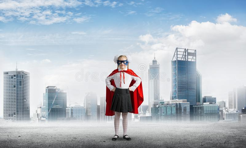 Girl power concept with cute kid guardian against cityscape background . Mixed media stock image