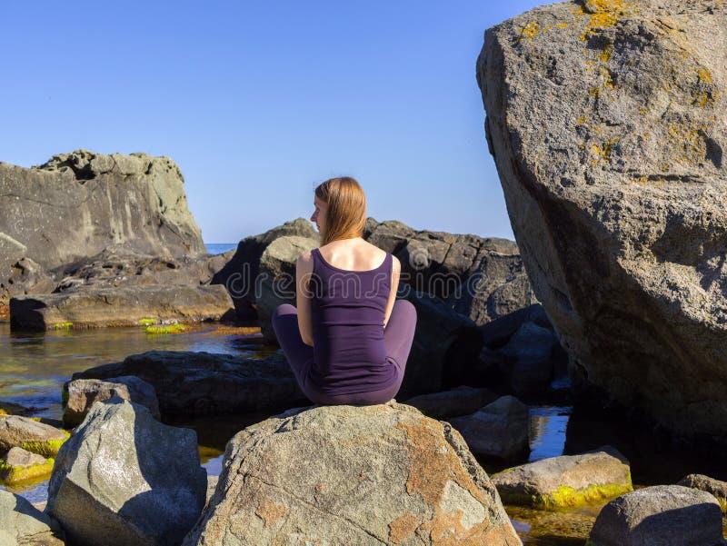 Girl practices yoga near the sea, on the rock, slow motion hd video. Woman practices yoga near the sea, on the rock, slow motion hd video stock photos