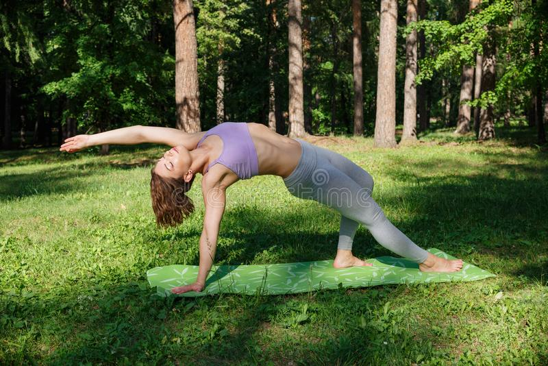The girl practices yoga in the park on a sunny day royalty free stock photography