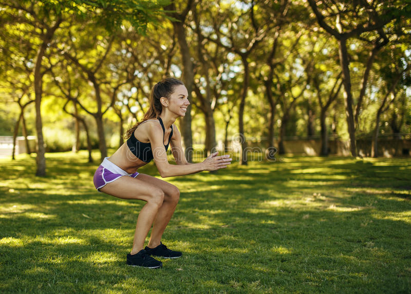 Girl practicing sport doing squat in the park. Beautiful caucasian girl practicing sport doing squat working out in the park summer morning royalty free stock photos