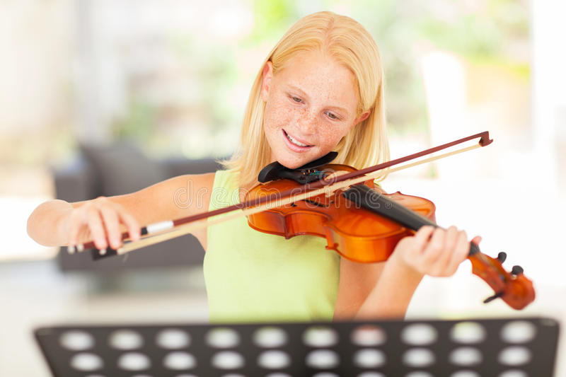 Girl practicing violin. Pretty preteen girl practicing violin at home royalty free stock images