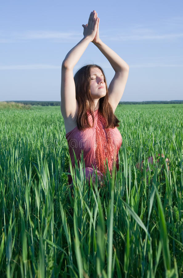 Girl practicing yoga. Beautiful young girl practicing yoga against blue sky stock photo