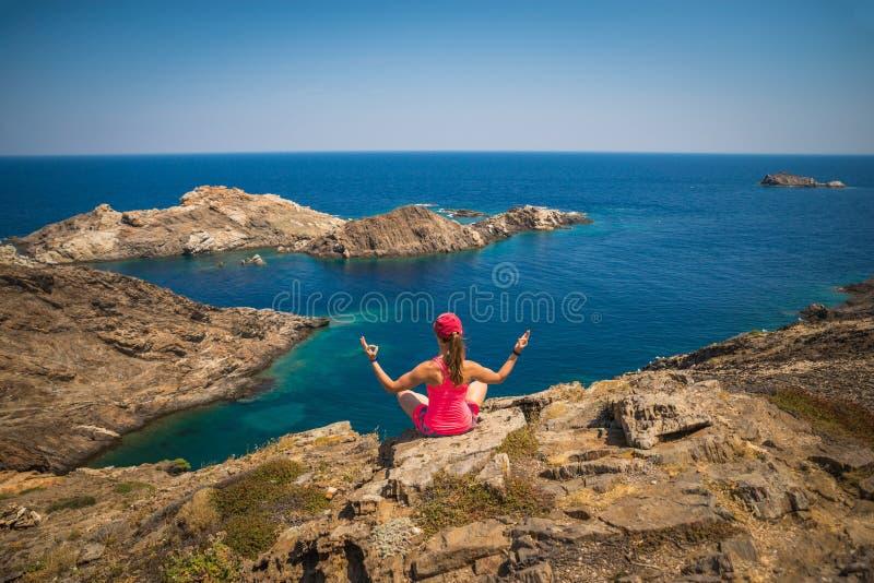 Girl practicing yoga above the sea stock photos