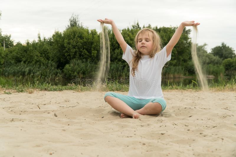 Girl practicing yoga on the beach. Toned image royalty free stock image
