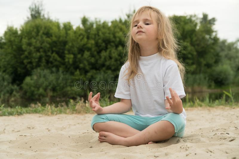 Girl practicing yoga on the beach. Toned image stock photo