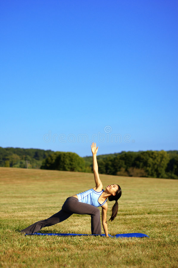 Girl Practicing Yoga In Field. Girl practicing yoga in a summer meadow royalty free stock images