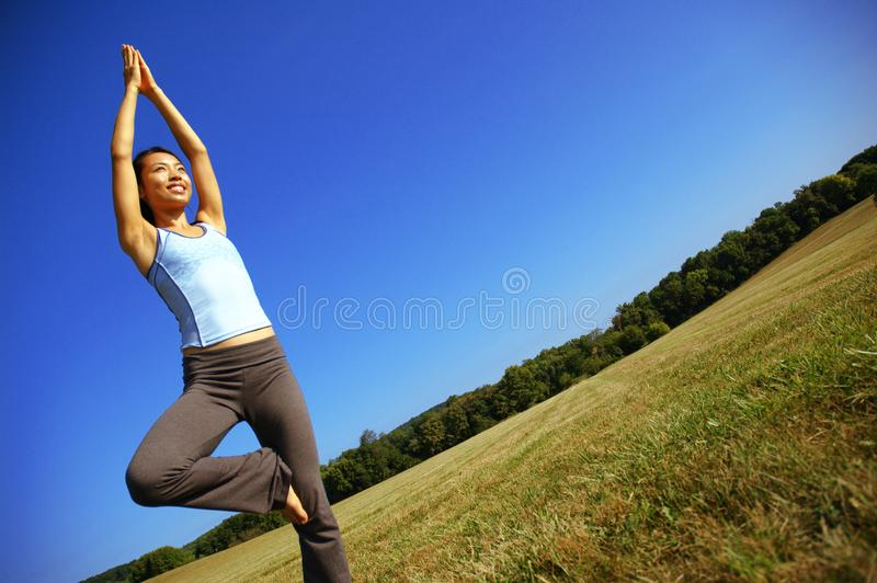 Girl Practicing Yoga In Field royalty free stock image
