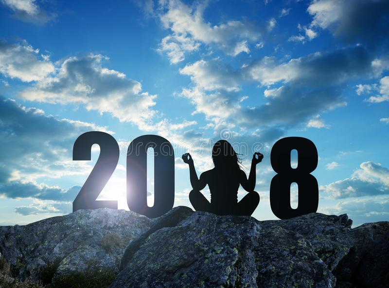 Girl practicing yoga on rock in the New Year 2018. royalty free stock image