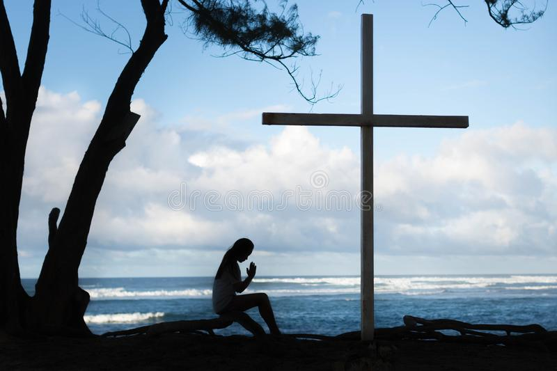 Girl praying to God in front of a cross with a beautiful blue ocean background. Silhouette of girl praying to large cross. Ocean in the background with religon stock images