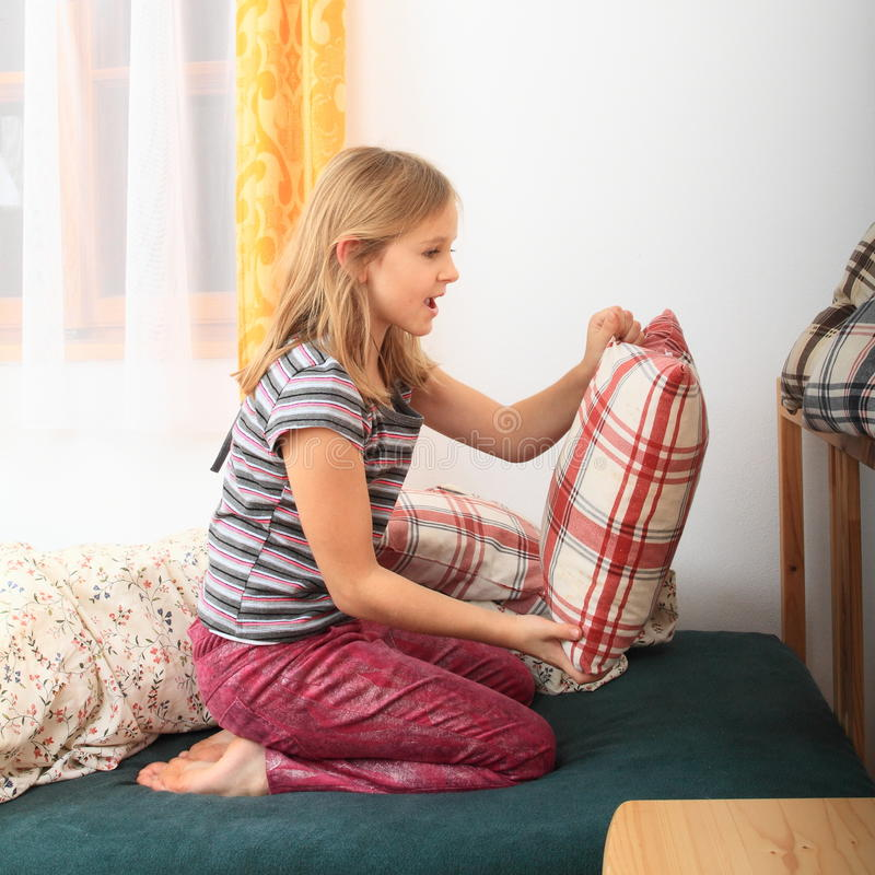 Girl prepairing bed for sleeping royalty free stock photography