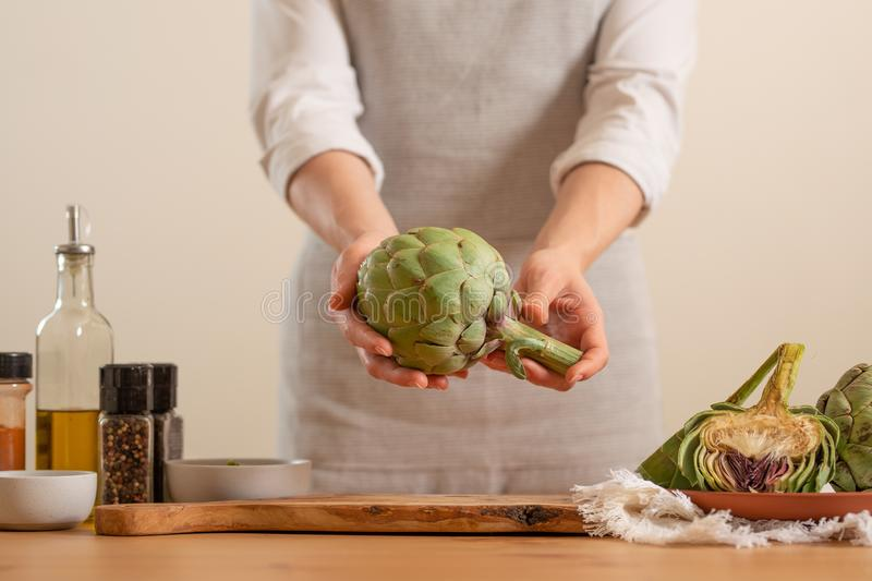 The girl prepares the artichoke, and holds it in her hands on a light background. Healthy eating concept. close-up.  royalty free stock images