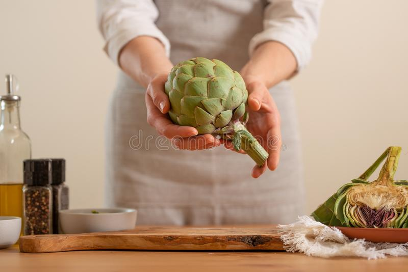The girl prepares the artichoke, and holds it in her hands on a light background. Healthy eating concept. close-up.  royalty free stock photo