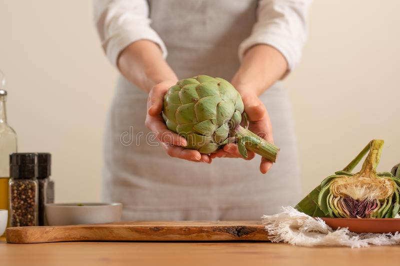 The girl prepares the artichoke, and holds it in her hands on a light background. Healthy eating concept. close-up.  stock images