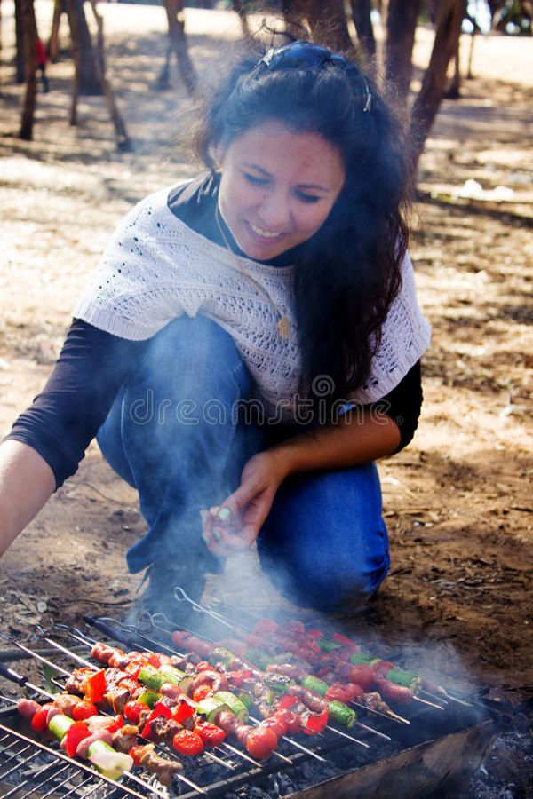 Girl prepares skewers. royalty free stock image