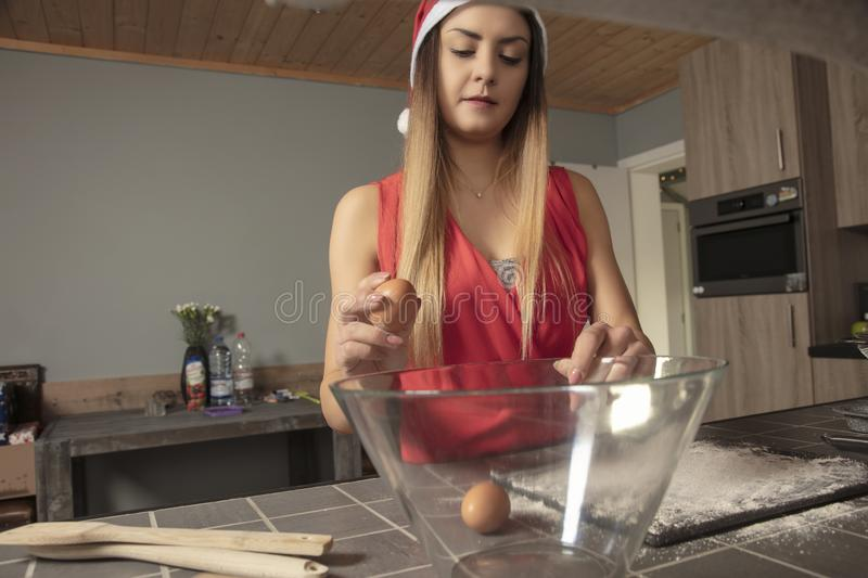 Girl is preparing cake for Christmas, putting eggs , front view stock image