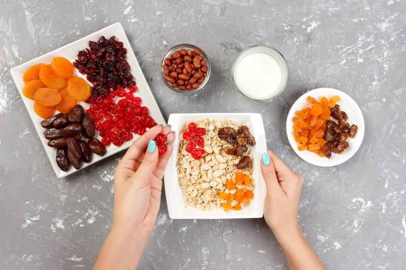 The girl is preparing her muesli for breakfast. The girl puts herself a dried fruit in oatmeal porridge. Useful and healthy breakf. Ast on a gray background, top royalty free stock image