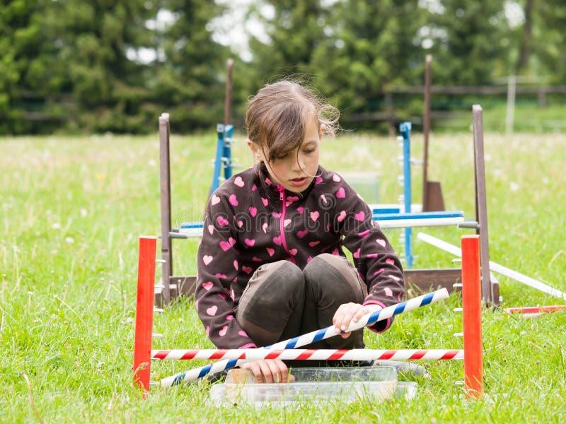 Girl preparing hurdle for bunny jumping stock images