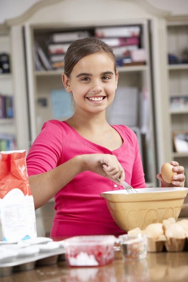 Girl Preparing Ingredients To Bake Cakes In Kitchen royalty free stock photos