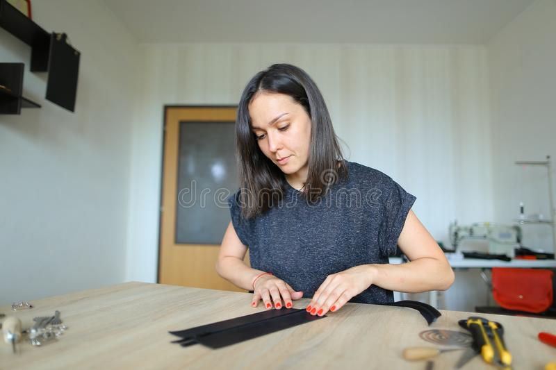 Girl preparing leather for making purse. Female carefully preparing leather for making black purse. Young woman decided to start business and rented room for stock photos