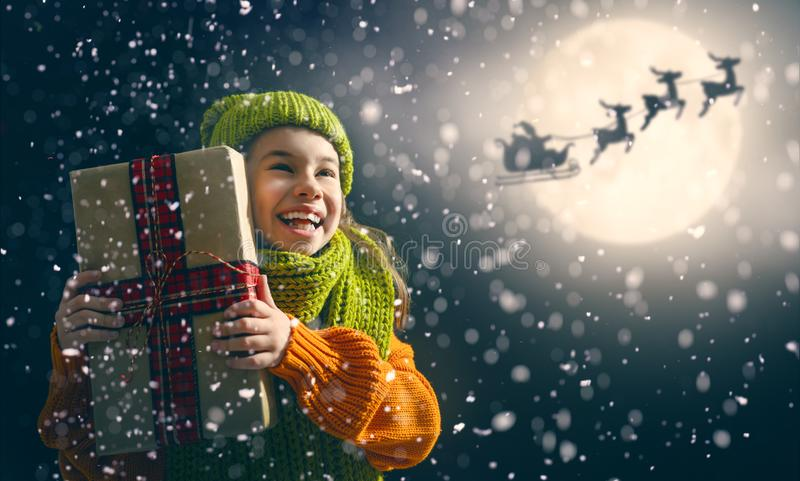 Girl with present at Christmas. Merry Christmas! Cute little child with xmas present. Santa Claus flying in his sleigh against moon sky. Happy kid enjoy the stock photography