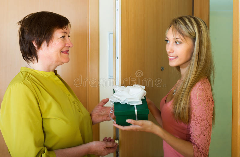 Girl presenting a gift. Young girl presenting a gift to elderly female indoor stock photo