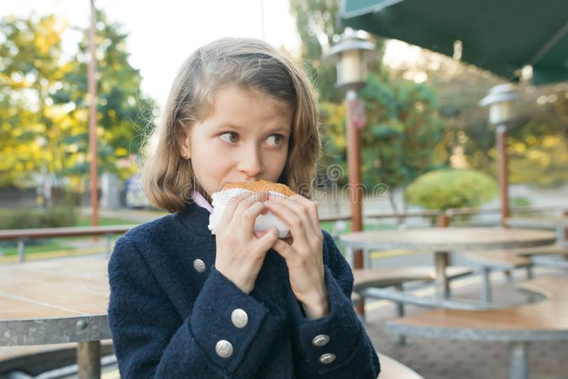 Girl primary school student eats burger, sandwich at an outdoor cafe royalty free stock images