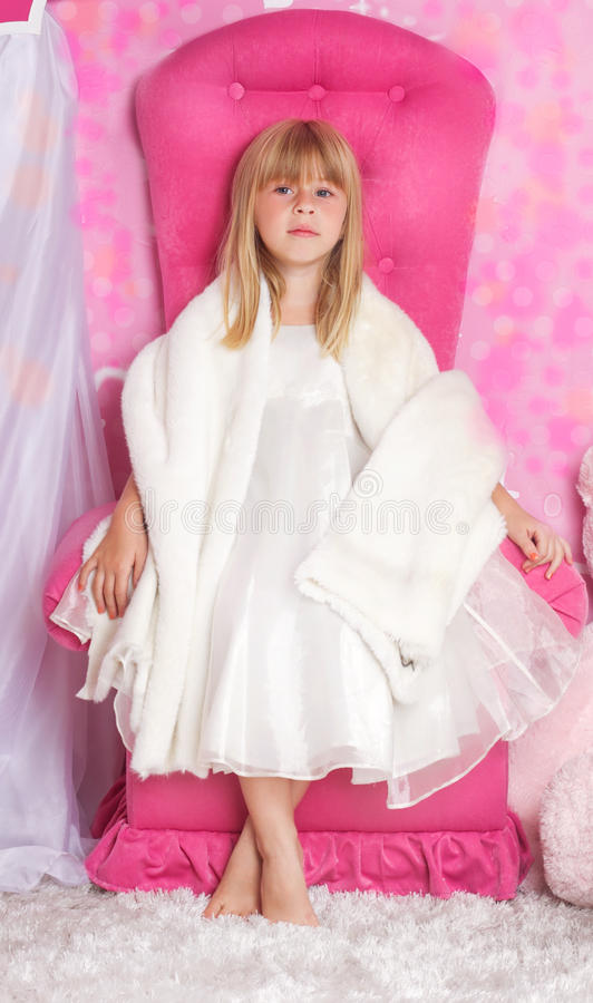 Girl princess is sitting on a pink throne stock images
