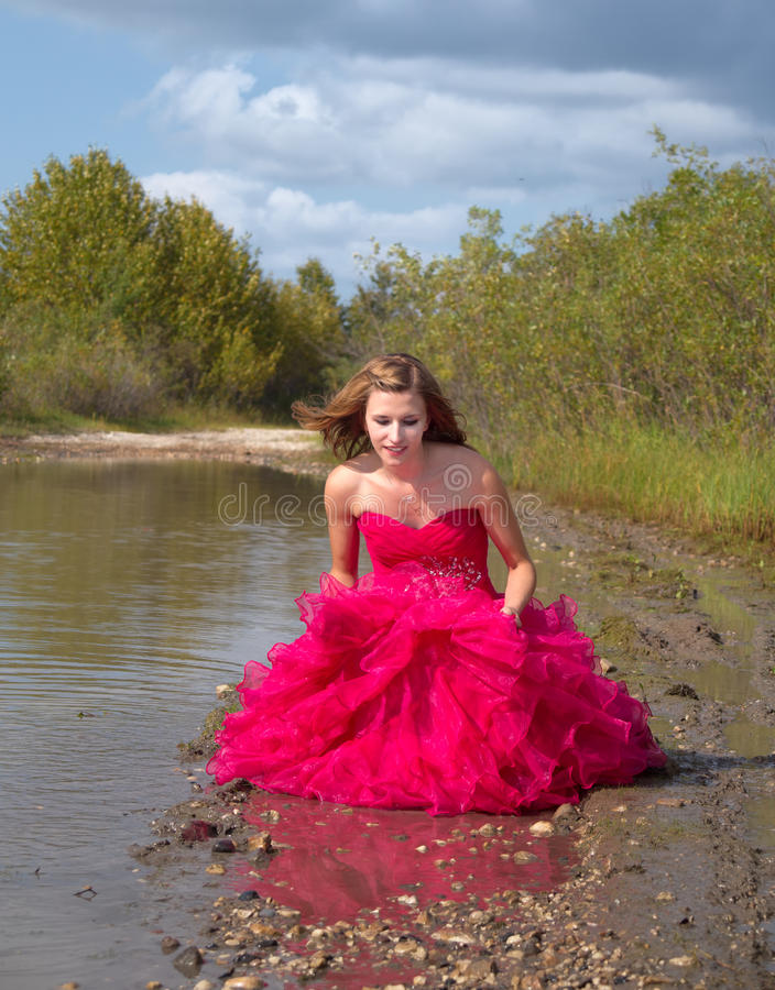 Girl in prom dress playing in the mud stock images
