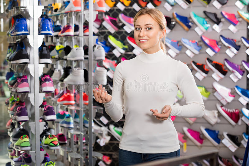 Girl promoting shoes in the sport boutique stock photo