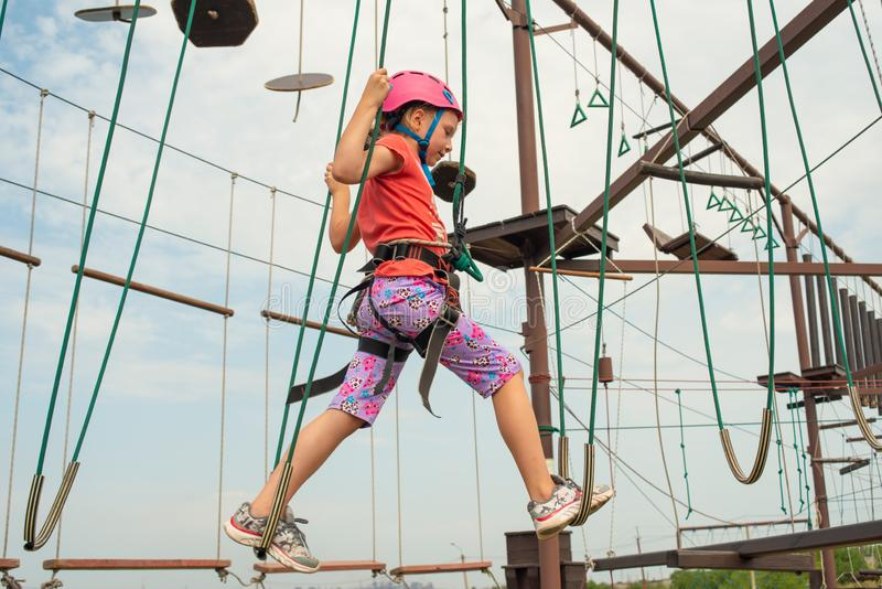 The girl in protective and safety clothing passes over a hanging bridge in a sports park, holding the side ropes stock photos