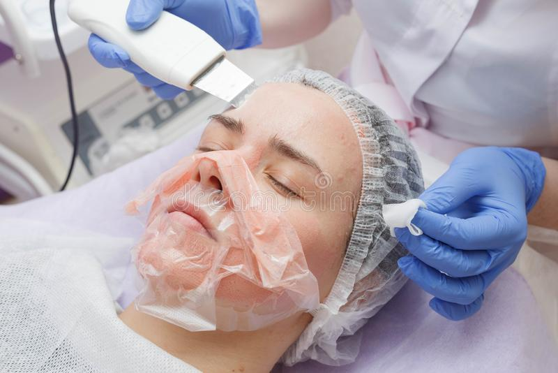 The girl is provided with an ultrasound skin cleaning service in the beauty salon stock photo