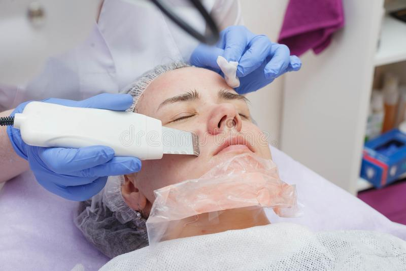 The girl is provided with an ultrasound skin cleaning service in the beauty salon stock image