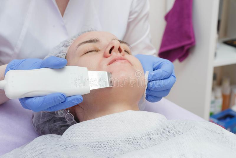 The girl is provided with an ultrasound skin cleaning service in the beauty salon stock photography