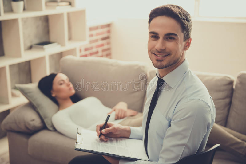 Girl at the psychologist. Handsome psychologist is making notes, looking at camera and smiling while girl is talking about her problems stock image