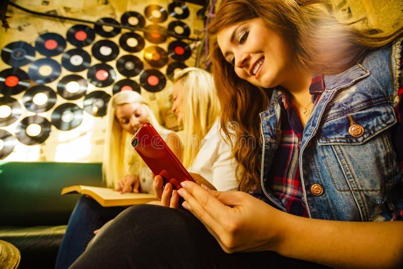 Girl in pub using smart phone stock image