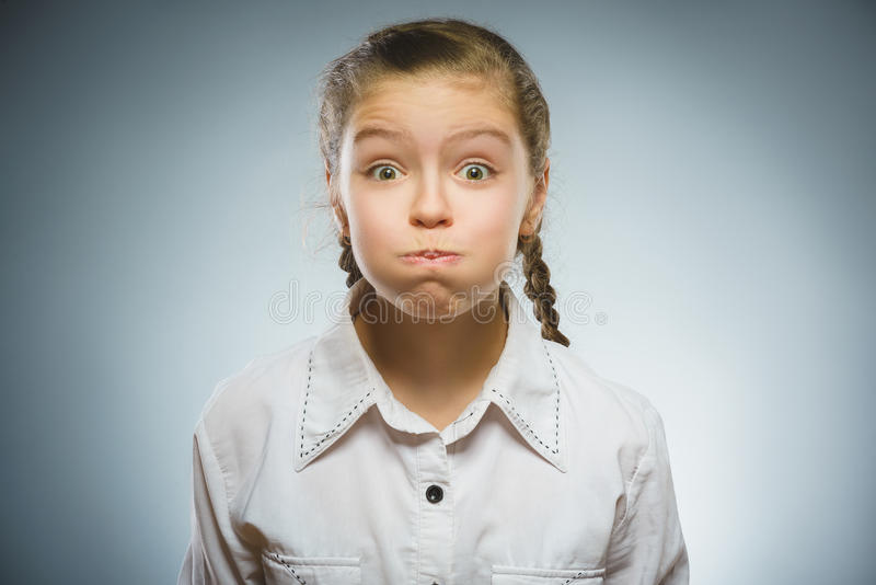 The girl puffed out her cheeks. On grey background stock photo