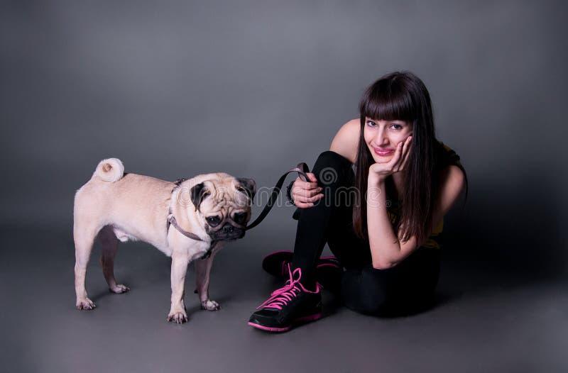 Girl With Pug Dog In Studio Stock Image