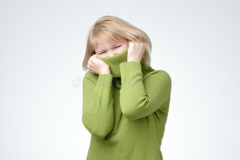 Girl pulling her trendy green sweater over head having fun. Woman being childish disappearing in her clothes looking from underneath stock image