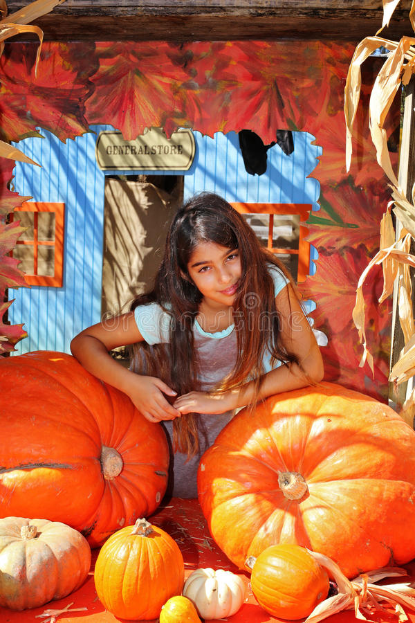Girl pumpkin patch. Girl leaning on 2 big pumpkins at a farm stock image