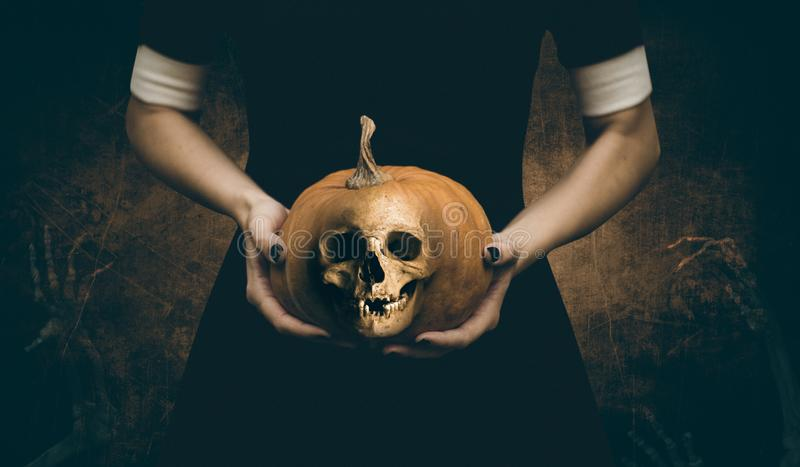 Girl with pumpkin skeleton head in her arms royalty free stock image