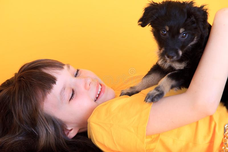 Girl with puppy. A girl happily playing with her cute puppy royalty free stock image