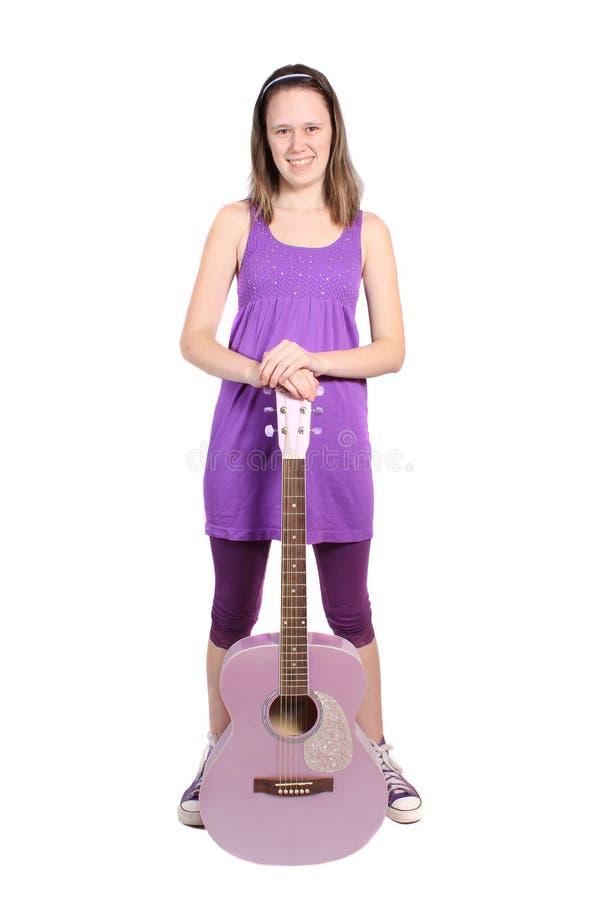 Girl with purple accoustic guitar. Teenaged girl standing holding a purple accoustic guitar stock photo