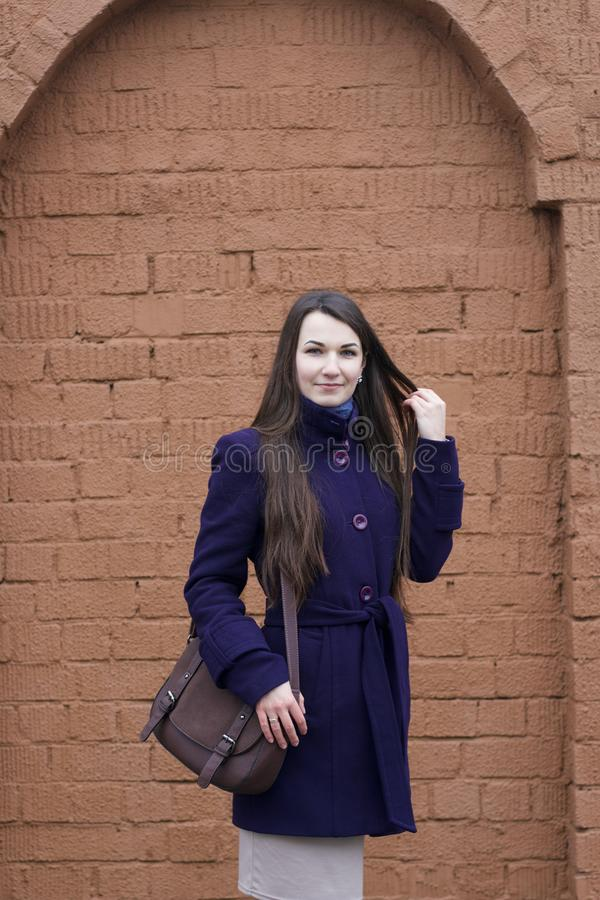 Girl in a purple coat posing on a background of a brown brick wall. Straightens hair with hand.  stock images