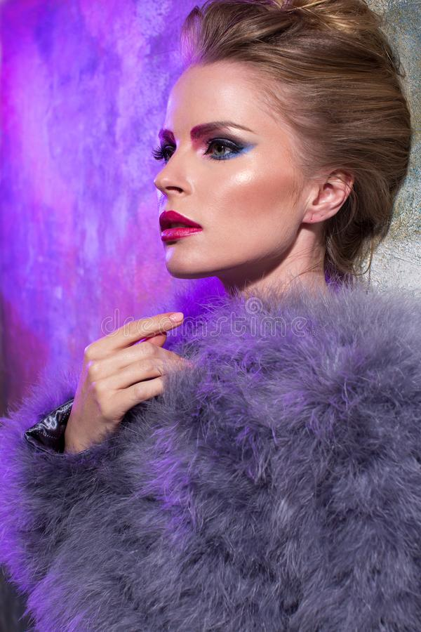 The girl in the purple coat from textured walls. The blonde in a purple fur coat stands by the textured wall, with a beautiful make-up and hairstyle stock photos